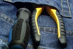Ställ in av facket för plattång för handhjälpmedelskruvmejseln det gula svarta av bakgrund för grunge för jeansnärbildbakgrund royaltyfri fotografi