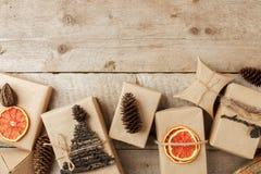 Ställ in av gåvaasken i hantverkpapper med naturlig garnering på tappningträbakgrund, gåvaferiebegrepp Nollförlorad livsstil, royaltyfri foto