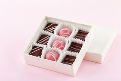 Ställ in av lyxiga handgjorda konfektar i gåvaask på pastellfärgad rosa bakgrund royaltyfria foton