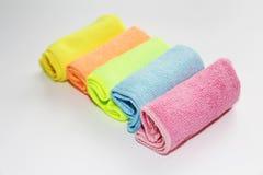 Ställ in av mång--färgade microfibertrasor för att göra ren Fem kulöra handdukar på en vit bakgrund royaltyfria foton