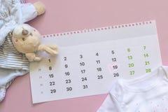 Ställ in av nyfödd tillbehör i förväntan av barnet - kalendern med cirklat nummer 19 nitton, behandla som ett barn kläder, leksak royaltyfri bild