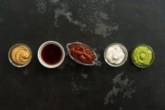 Ställ in av olika såser i bunkar i rad på en svartstenbakgrund Senapsgult sås, tomat, wasabi, majonnäs, sojaböna , Bästa sikt, arkivfoton