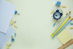 Ställ in av skolabrevpapper tillbaka till skola: blyertspennor klocka, notepad, linjal på gul bakgrund utbildning kurs royaltyfri foto