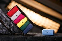 Ställ in av tillfälliga sockor av olika färger i svart gåvaask en royaltyfri bild