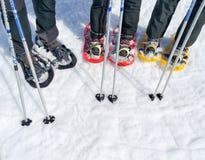 ställ in av tre par av snöskor, eller racket av snö och två skidar poler av en grupp av sportfolk på snön som är klar att gå på royaltyfri foto