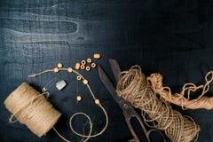 Ställ in för handarbete: saxen och skeinjute tvinnar på svart bakgrund Top beskådar Royaltyfria Foton
