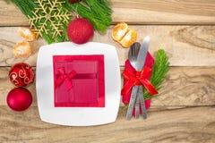 Ställ in för jultabeller, tangerin, garneringar, gran och en platta med en gåva och ett bestick festlig bakgrund bakgrundsfärger  arkivbild