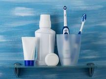 Ställ in för muntlig omsorg och två tandborstar i ett exponeringsglas Arkivbild