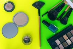 Ställ in skönhetsmedelmakeup, borsten, ögonskugga på guling-gräsplan bakgrund royaltyfri bild
