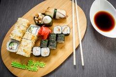 Ställ in sushirullar, soya och pinnar på en grå bakgrund Top beskådar Lekmanna- lägenhet traditionell mat royaltyfria bilder