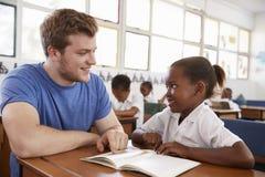 Ställa upp som frivillig upp lärareportionskolflickan på hennes skrivbord, slut arkivfoto