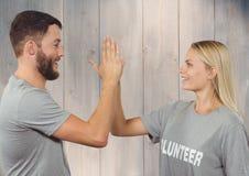 Ställa upp som frivillig par i tshirten som till varandra ger höjdpunkt fem Royaltyfri Foto