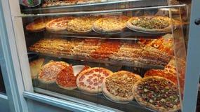 Ställa ut mycket av stora, färgrika och välfyllda pizza arkivfoto