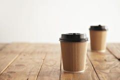 Ställde bort pappers- koppar in för brunt papptagande med svarta lock Royaltyfri Foto