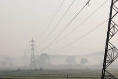 Ställde elektriska poler in för hög spänning i risfältet med mist i t Fotografering för Bildbyråer
