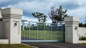 Ställde portar in för ingång för egenskap för privat uppehåll för metallkörbana i tegelstenstaket med trädgårds- träd i bakgrund royaltyfri bild