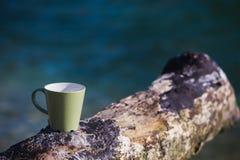 Ställe för kaffekopp på ett stycke av trä på bakgrundshavet arkivfoton
