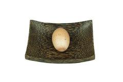 Ställen för ett ägg på en wood platta på vit bakgrund som isoleras Royaltyfria Bilder