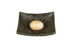 Ställen för ett ägg på en wood platta på vit bakgrund som isoleras Fotografering för Bildbyråer