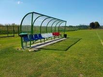 Ställen för lagledare och reservspelare på fotbollfältet Plast- färgade bänkar under en markis av genomskinlig glasfiber Beträffa royaltyfri fotografi