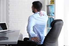 Ställingsbegrepp Man lidande från tillbaka smärtar, medan arbeta med bärbara datorn royaltyfri fotografi