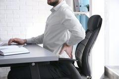 Ställingsbegrepp Man lidande från tillbaka smärtar, medan arbeta med bärbara datorn på kontoret royaltyfri fotografi