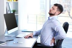 Ställingsbegrepp Man lidande från tillbaka smärtar, medan arbeta med datoren royaltyfri foto