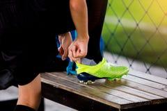 Ställning för fotbollspelare och sätta sportskosnöre arkivfoton