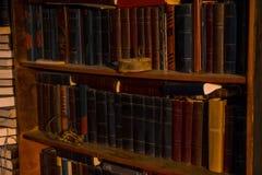 Ställning för gamla böcker på trähyllor som bordlägger med böcker på hyllan är ett gammalt rostigt lås och en grupp av tangenter, arkivbilder
