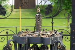 Ställning för kyrkastearinljus med mynt i kyrkogården av helgedomen Arkivfoto