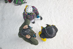 Ställning för tre idrottsman nen, innan att starta på en snowboard Arkivfoto