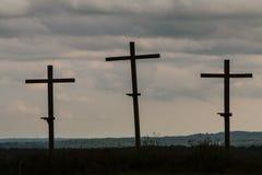 Ställning för tre träkors mot en mörk illavarslande himmel Arkivbilder