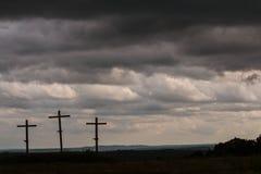 Ställning för tre träkors mot mörka illavarslande stormmoln Arkivfoto