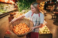 Ställning för ung kvinna på fruktaskar i livsmedelsbutik Hon rymmer korgen med apelsiner och ser dem Positiv lycklig arbetare arkivbild