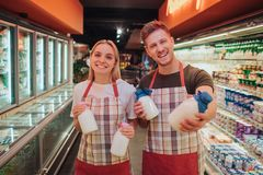 Ställning för ung man och kvinnai livsmedelsbutik- och mejerihylla De rymmer glasflaskor av mjölkar och poserar på kamera positiv royaltyfri bild