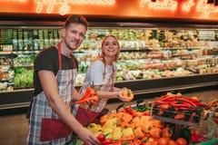 Ställning för ung man och kvinnapå grönsakkorgen i livsmedelsbutik De sätter några peppar och poserar på kamera positivt fotografering för bildbyråer