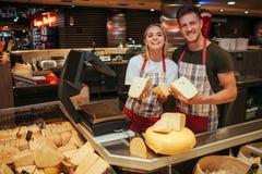 Ställning för ung man och kvinnapå osthyllan i livsmedelsbutik Lyckliga positiva arbetare poserar på kamera och leende Ost royaltyfria bilder