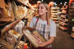 Ställning för ung man och kvinnapå pastahyllan i livsmedelsbutik Hon rymmer lyckligt flera att förpacka av den och leendet Bara i fotografering för bildbyråer