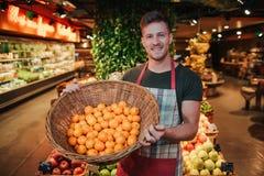 Ställning för ung man på fruktaskar i livsmedelsbutik Han rymmer korgen med apelsiner och poserar på kamera Positiv ung man royaltyfria bilder