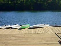 Ställning-upp Paddleboards på en skeppsdocka på sjön Arkivbild