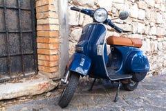 Ställningar för sparkcykel för Vespa PX 150 för klassiker parkerade blåa Fotografering för Bildbyråer