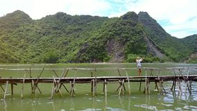 Ställningar för surrsiktsflicka på bron gör Selfie mot ön lager videofilmer