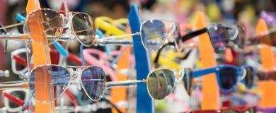 Ställningen med barns solglasögon arkivfoton