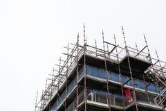 Ställninghöjdpunkt som resas upp på vit klar himmel för byggnadskonstruktionsplats royaltyfri foto