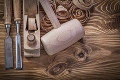 Stämjärn som rakar träklubban för plana shavings på wood brädeconst Arkivfoto