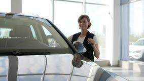 Stämmer den nya bilen för ägaren, shower i händer, nära motorfordonet som är lyckligt lager videofilmer