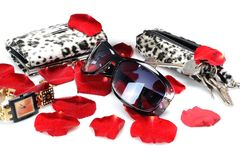Stämmer röda kronblad för en ros, tillbehören för kvinna` s, solglasögon, klockan, plånbok, i stilleben på en vit bakgrund fotografering för bildbyråer