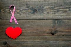 stämpel för fund för find för bröstcancerbotslagsmål post Mammalogybegrepp Symboliskt rosa band nära hjärtatecken på mörkt träutr arkivfoto