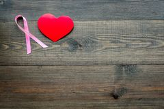 stämpel för fund för find för bröstcancerbotslagsmål post Mammalogybegrepp Symboliskt rosa band nära hjärtatecken på mörkt träutr fotografering för bildbyråer