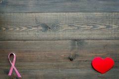 stämpel för fund för find för bröstcancerbotslagsmål post Mammalogybegrepp Symboliskt rosa band nära hjärtatecken på mörkt träutr royaltyfri fotografi